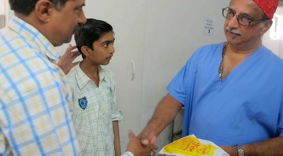 Ashiket presenting sweets to Dr George Teturswamy